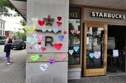 In this Thursday, June 4, 2020 file photo, a woman looks at the plywood covering the windows of a Starbucks store in downtown Naperville, Ill., as Naperville residents used hearts to post messages in support of the Black Lives Matter movement