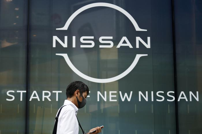 A man walks by new logo of Nissan seen at the automaker's showroom in Tokyo Tuesday, July 28, 2020