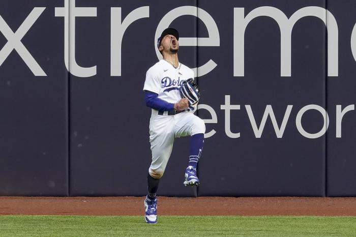 Los Angeles Dodgers right fielder Mookie Betts celebrates after robbing Atlanta Braves' Marcell Ozuna of a home during the fifth inning in Game 6 of a baseball National League Championship Series Saturday, Oct. 17, 2020, in Arlington, Texas. (AP Photo/Tony Gutierrez)