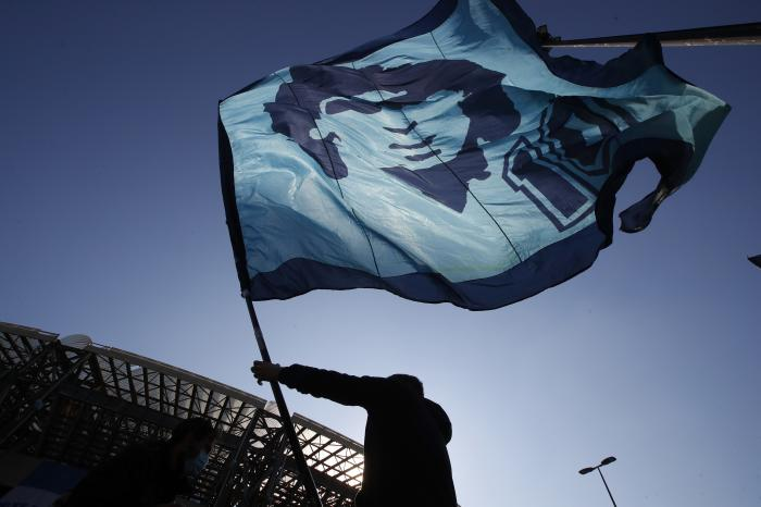A man waves a flag commemorating soccer legend Diego Maradona outside the San Paolo stadium, in Naples, southern Italy, Thursday, Nov. 26, 2020