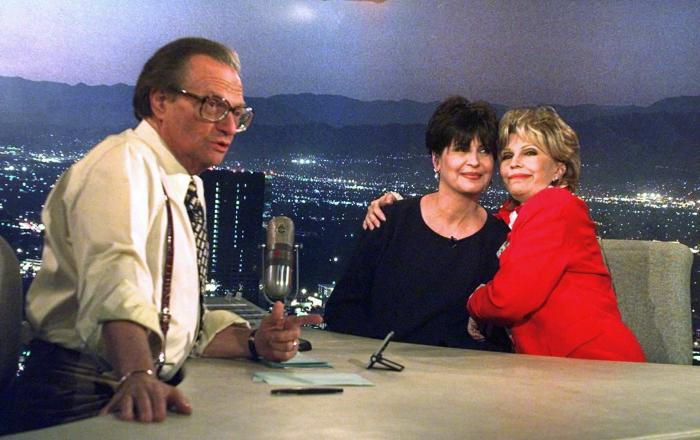 """Tina Sinatra, center, and Nancy Sinatra, right, daughters of the singer Frank Sinatra, joke around on CNN's Los Angeles set of """"Larry King Live"""" as host Larry King makes preparations."""
