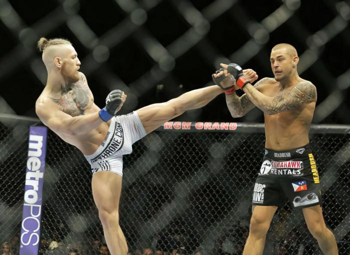In this Sept. 27, 2014, file photo, Conor McGregor, left, kicks Dustin Poirier during their mixed martial arts bout in Las Vegas.