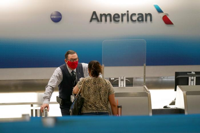 American Airlines ticket agent Henry Gemdron, left, works with a customer at Miami International Airport.