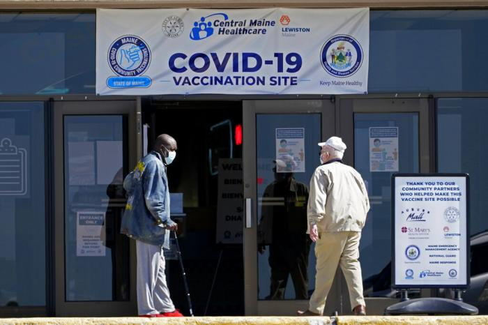 One man holds the door for another as they arrive at a COVID-19 vaccination clinic at the Auburn Mall in Auburn, Maine.