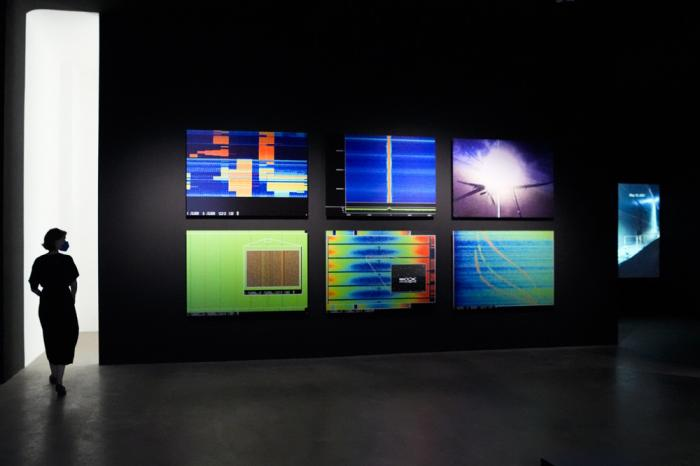 """A woman walks through an exhibition by American artist and filmmaker Laura Poitras, near the art work """"Anarchist"""" by Laura Poitras in collaboration with Henrik Moltke, at the N.K.B. gallery in Berlin, Germany, on Friday, June 18, 2021"""