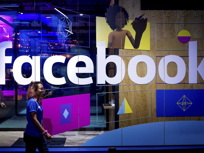 In this April 18, 2017, file photo, a conference worker passes a demo booth at Facebook's annual F8 developer conference, in San Jose, Calif.