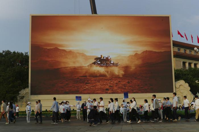 Attendees at a ceremony to mark the 100th anniversary of the founding of the ruling Chinese Communist Party pass by a screen depicting China's Mars spacecraft with its rover landing in Beijing on July 1, 2021